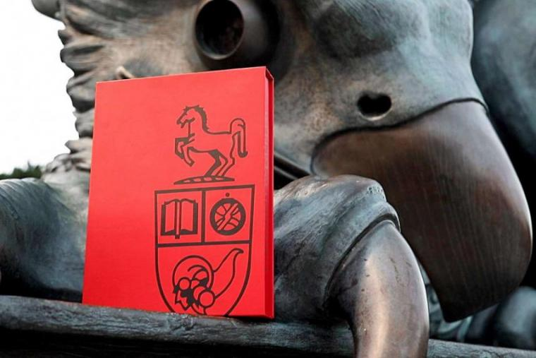 Image of Guelph Gryphon statue with graduation booklet resting on foot
