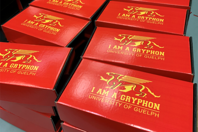 "Image of orientation week boxes, which are red with the U of G Gryphon and ""I am a Gryphon"" printed on them"