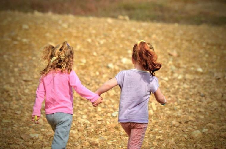 image of children holding hands and running in field