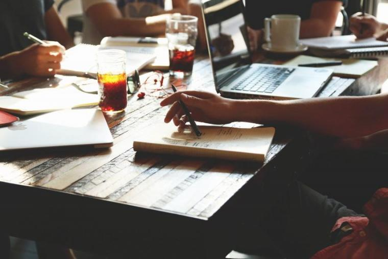 Image of people collaborating with papers across table