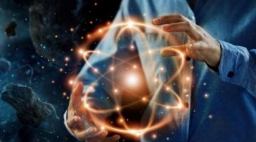 Person holding an illustration of an atom against the backdrop of space.
