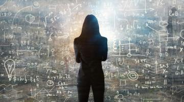 Silouette of a woman standing in front of a blackboard with mathematical equations written on it.