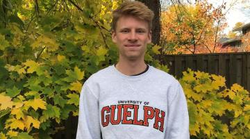 Image of Grant Doherty wearing a grey University of Guelph sweater with trees in background