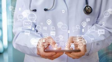 Composite image of person holding iPad in doctor's uniform with data emitting from screen