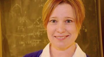 Physics Professor Joanne O'Meara in front of a chalkboard.
