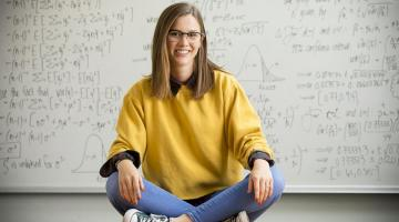 Image of student sitting on floor with legs crossed and math equations in background