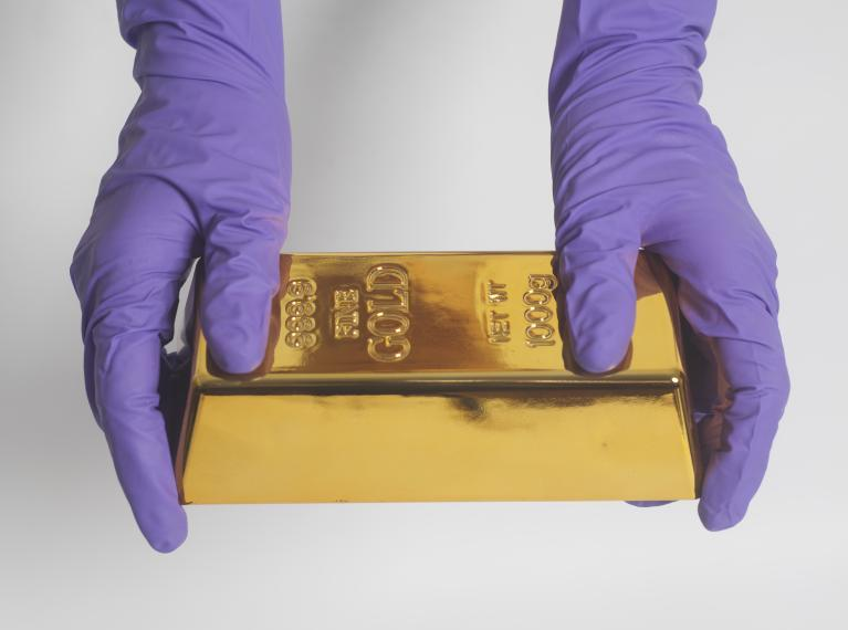 Gloved hands holding a bar of gold