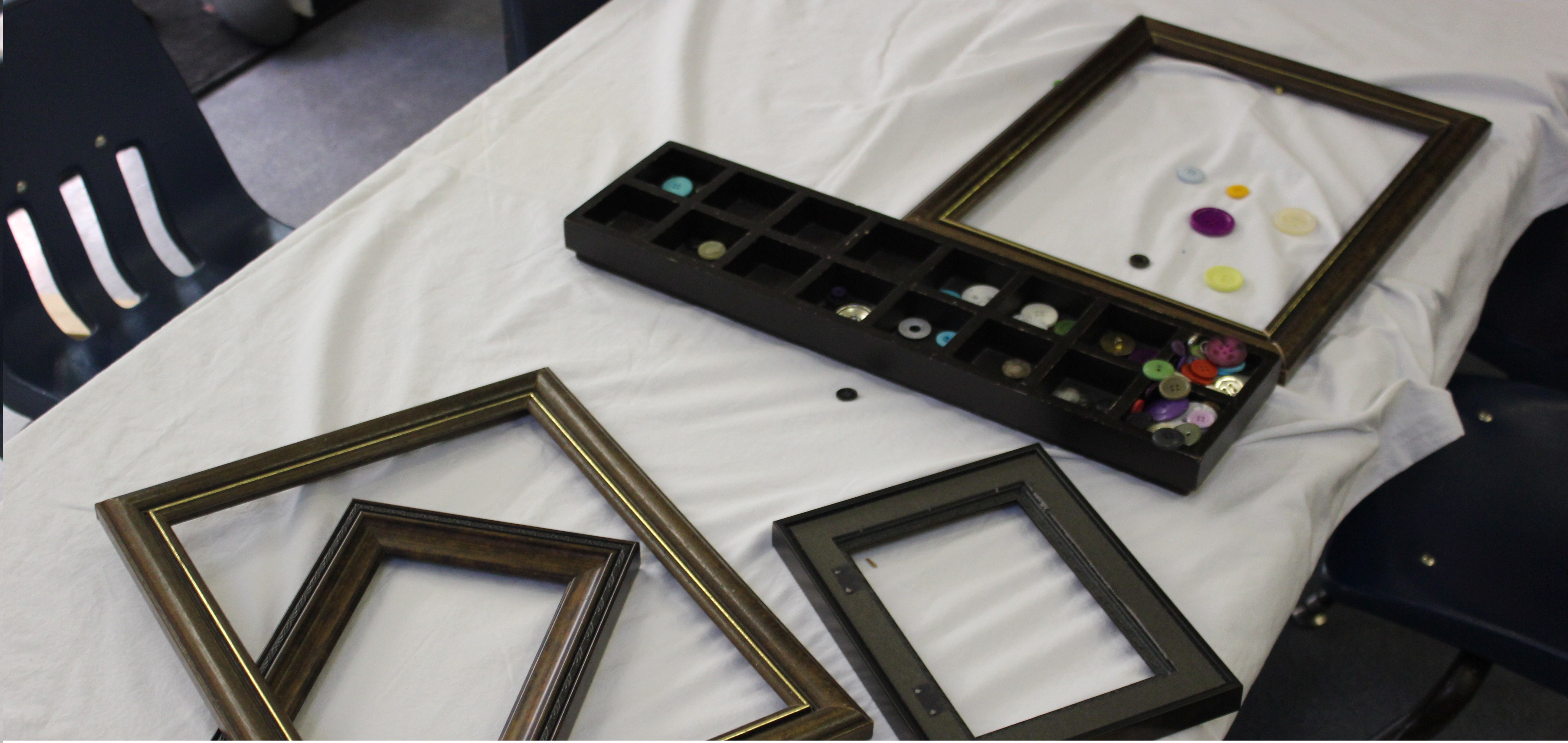 Picture frames and buttons on a table.