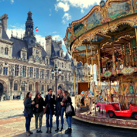 Students walk by a French hotel and carousel