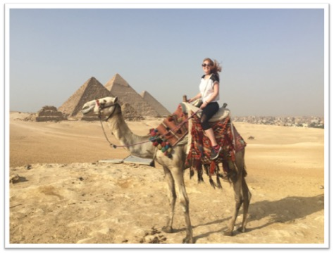 Photo of student on a camel in front of pyramids
