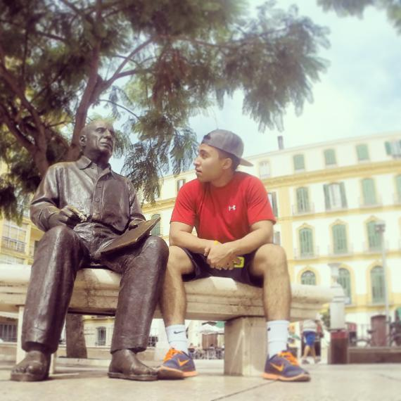 Student sitting beside a statue