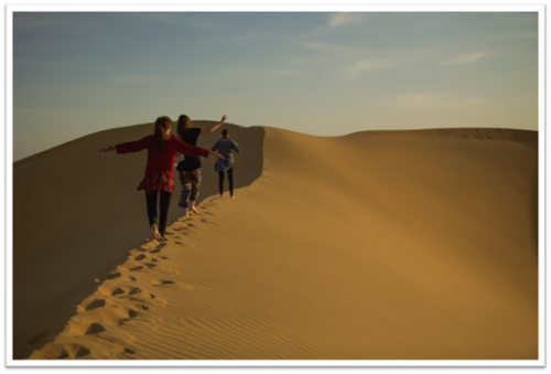 Three students walking along desert dunes