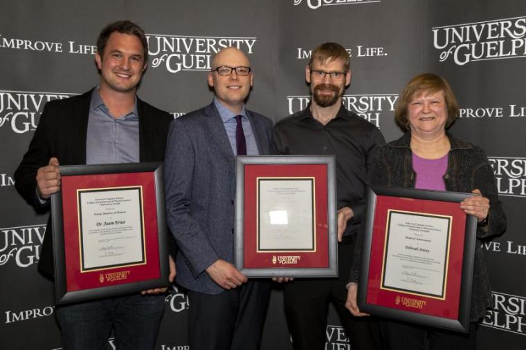 Honorees from left to right: Dr. Jason Ernst, Devin Gauthier, Mark George, and Dr. Deb Stacey [each holding a framed UofG award]