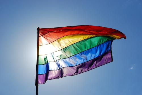 LGBTQ+ rainbow Pride flag flying on a flag pole