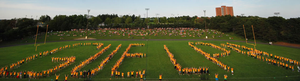 "Students forming the word ""Guelph"" on a football field"