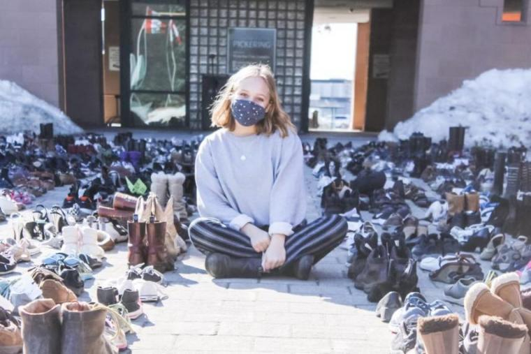 Ally Zaheer sitting amidst nearly 1,000 shoes placed outside city hall in Pickering in late February in protest to proposed development of provincially significant wetlands.