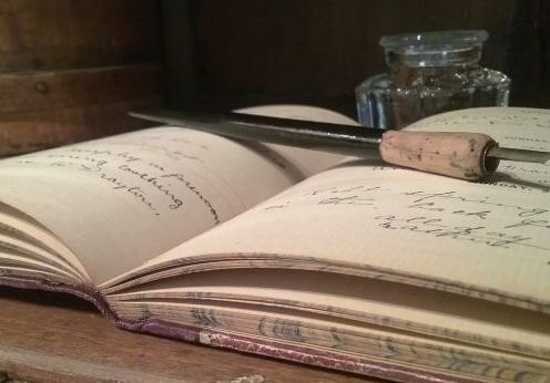 image of a historic diary with a pen