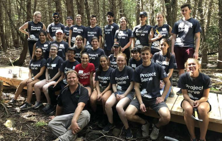 Dave Beaton sits with the Project Serve team that helped repair boardwalks along the Hanlon Creek trail in 2019