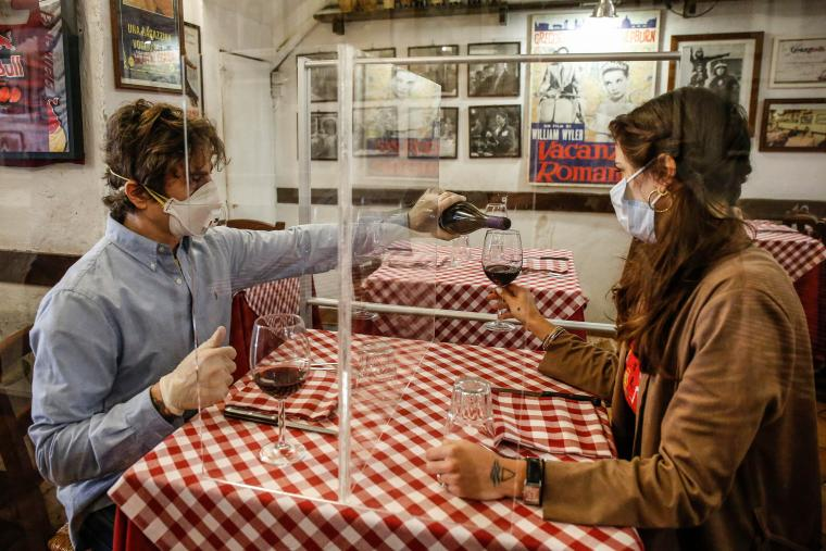 Picture of 2 people with masks sitting at a restaurant table.
