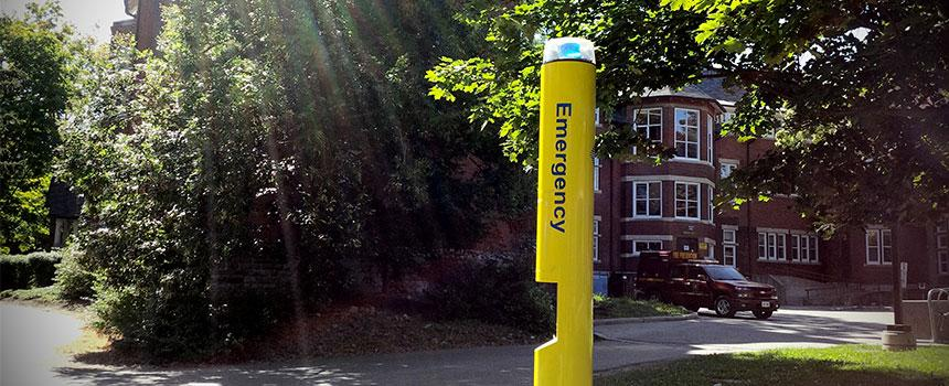 yellow emergency phone pole located across campus