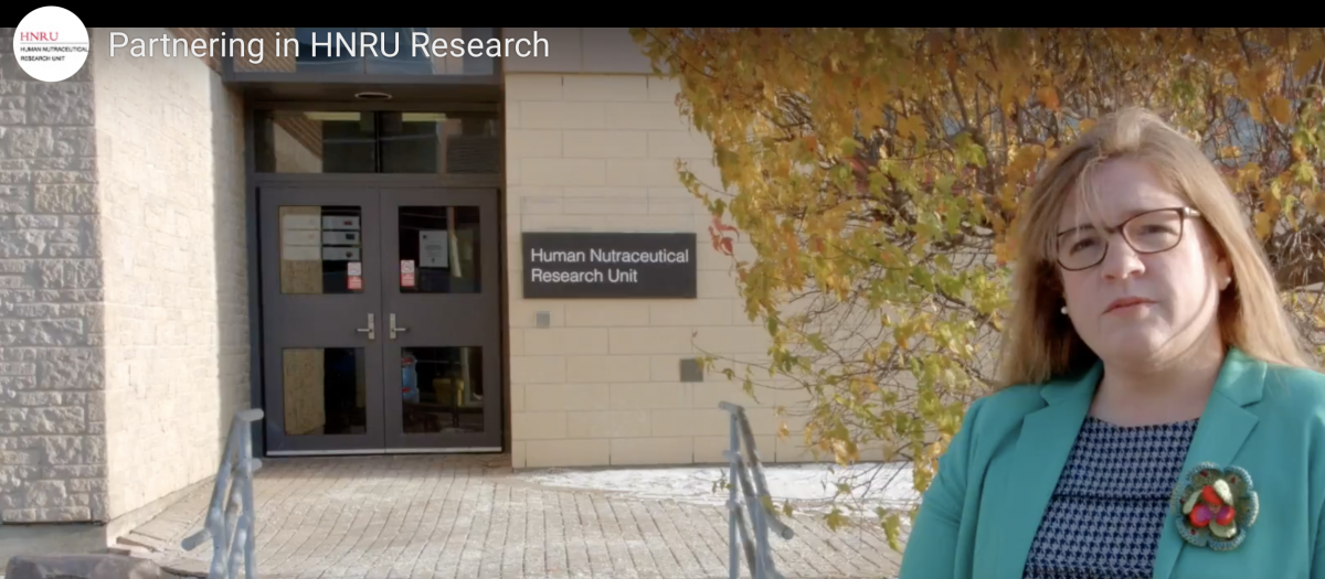 A photo of Dr. Amanda Wright, standing in front of the HNRU.