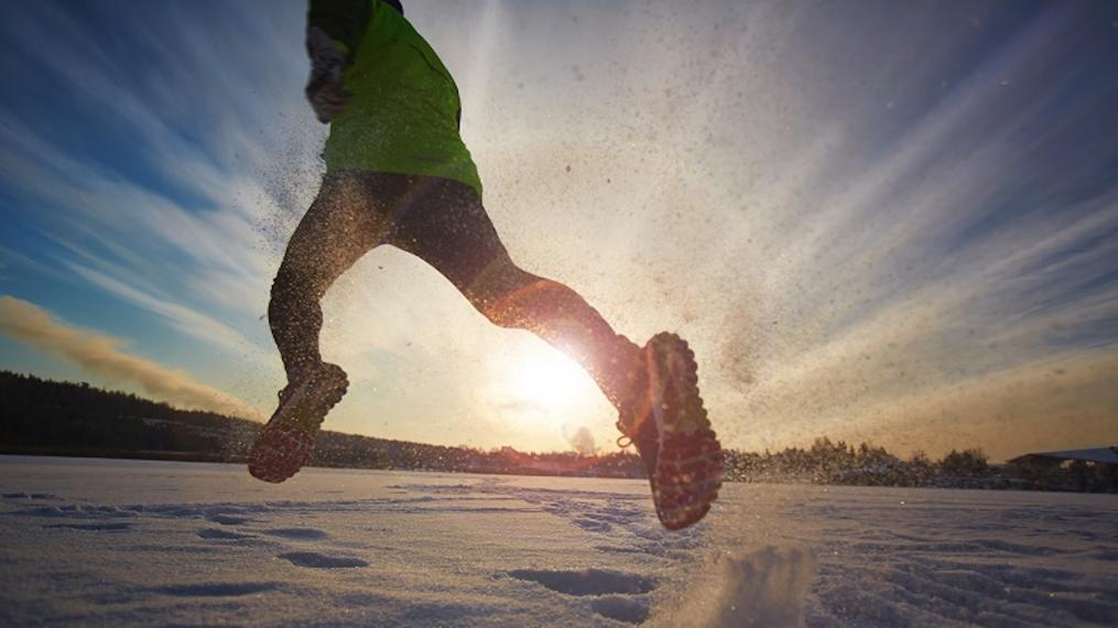 A photograph of a man running on snow