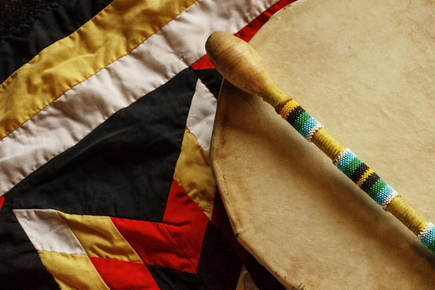 A rawhide hand drum and beaded drumstick sit on a star blanket made of red, yellow, white and black fabric.