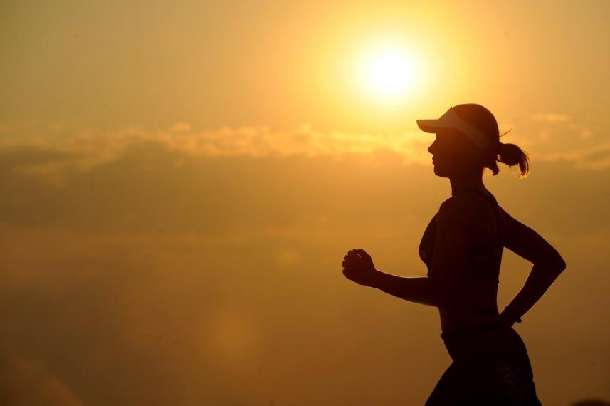 A photograph of a woman running at sunset