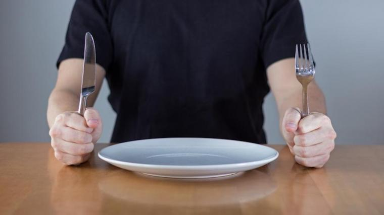 A photograph of a man with and empty plate and a knife and fork