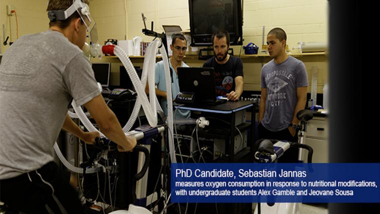 A photograph of a nutritional study. PhD candidate Sebastien Jannas measures oxygen consumption in response to nutritional modifications, with undergraduate students Alex Gamble and Jeovane Sousa.