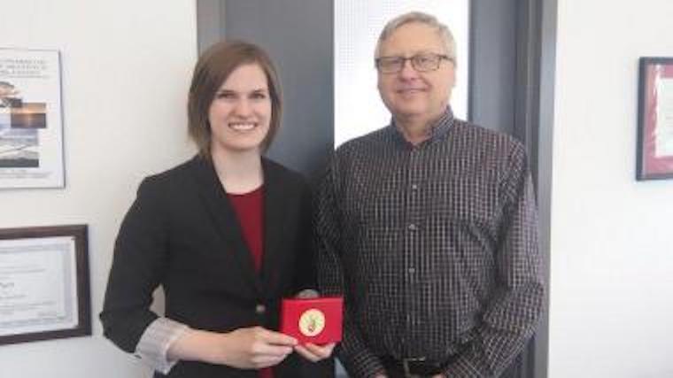 A photograph of Sandra Clark receiving an award.