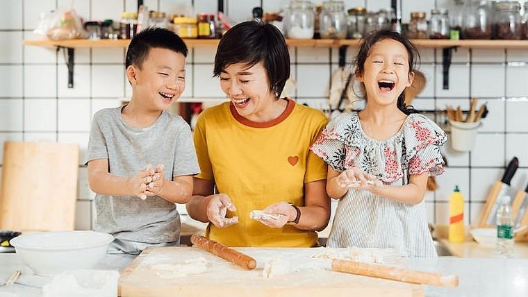 A photograph of a mother and children laughing and baking bread together