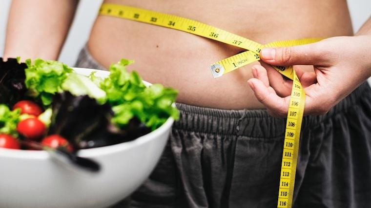 A photograph of a bowl of salad and a woman measuring her belly