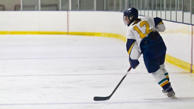 A photograph of a female hockey player on the ice in an icerink.