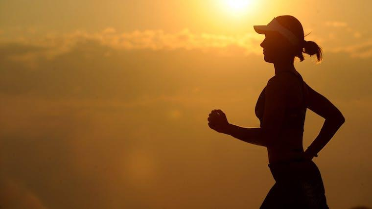 A photograph of a woman jogging at sunset