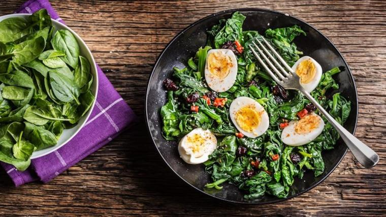 A photograph of a spinach salad with hard-boiled eggs.