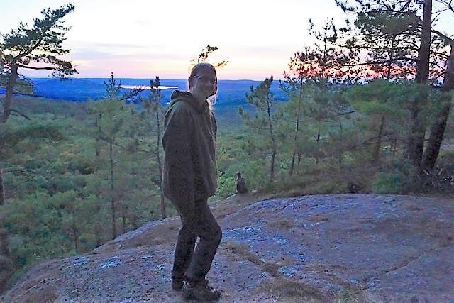 Dr. Leslie Rye standing on a cliff overlooking Algonquin Park at sunset