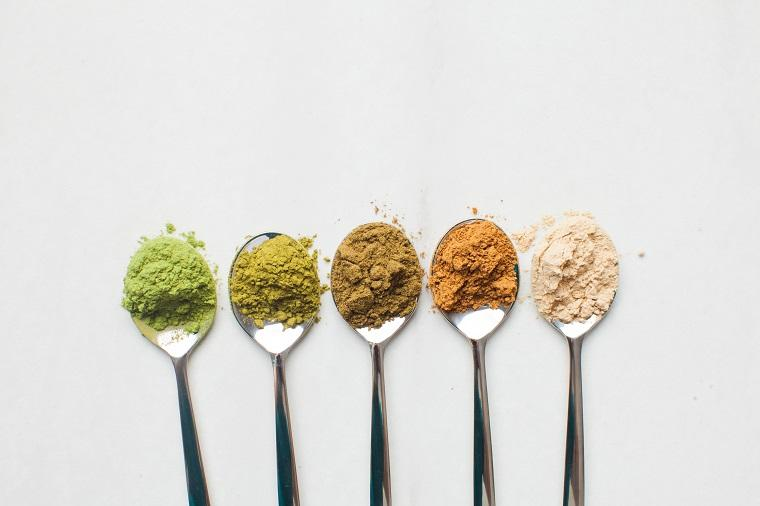 Spoons of different coloured protein powders