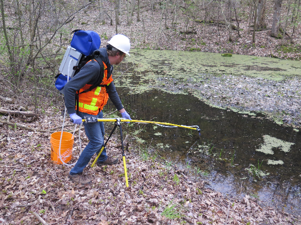 Photo of Scientist sampling water from pond in forest