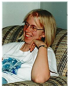 Photo of Leslie Rye. Sitting on a couch and smiling.