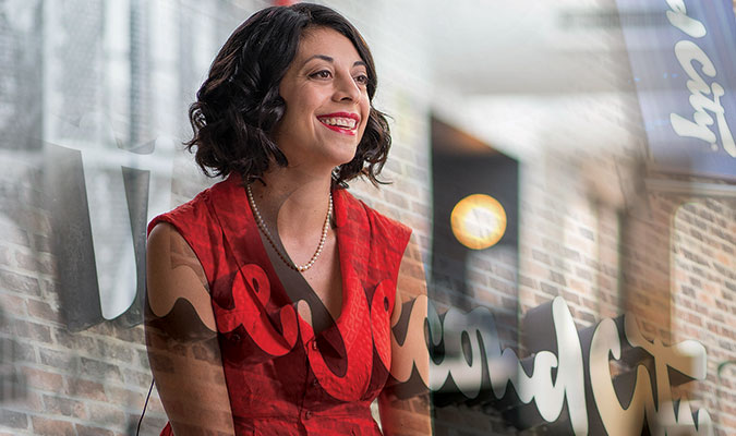 A sitting, smiling woman with red lipstick and short, dark, curly hair wearing a red dress and a white pearl necklace. Behind her is a brick wall and segments of a banner and an exterior theatre sign that read 'Second City'