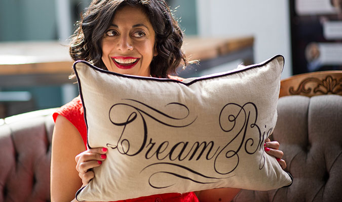 A woman shows her smiling and looking off-camera, while holding a beige couch cushion that reads 'Dream Big' in black lettering.