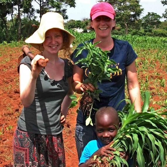 Nat and Kiera in Kenya with a little kid helping in the fieldwork