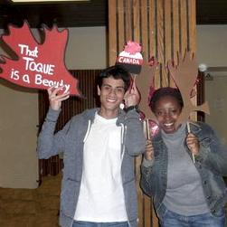 two students with cardboard cut outs of moose antlers and a toque