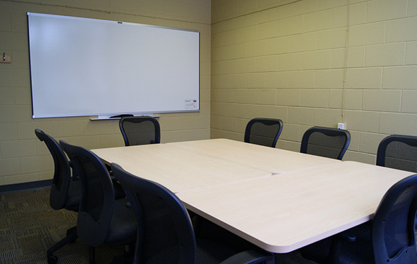 Large boardroom features centre table and whiteboard