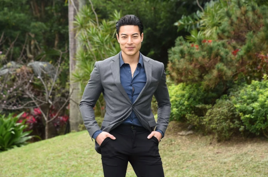 Chase Tang standing in front of green landscaping and bushes