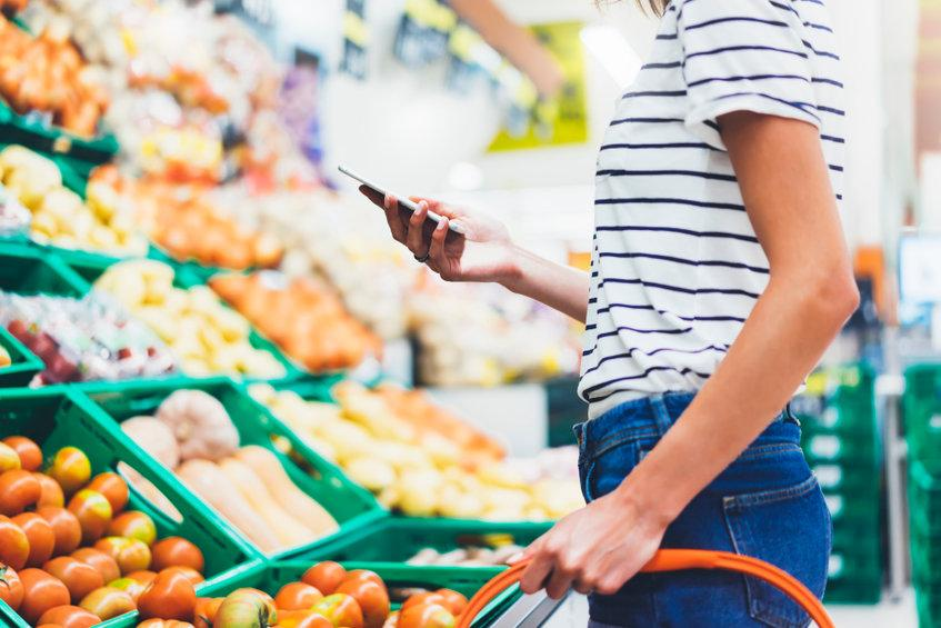 women using phone at grocery store