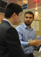 Two attendees discuss research in the Science Atrium