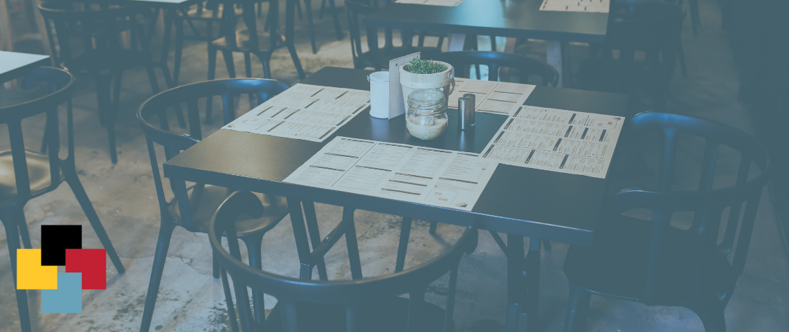 Image of a restaurant table with menus on it with a blue overlay and the four square Lang logo in the bottom left corner.