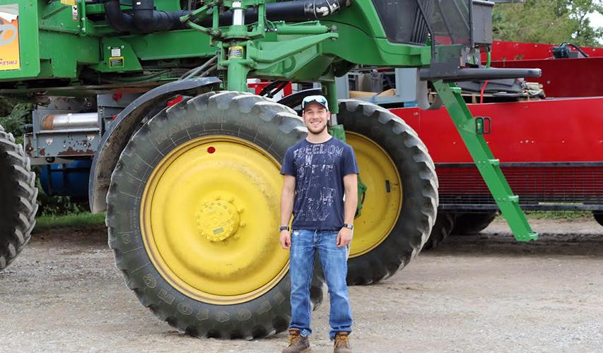 Dylan Sher standing in front of tractor